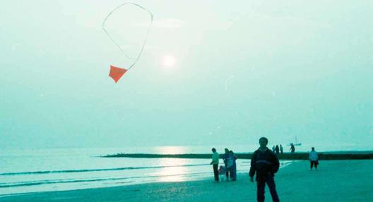 """""""Norderney: Strand bei Ebbe, mit Drachen und Sonnenuntergang"""" (1986), Willy Pragher, Landesarchiv Baden-Württemberg (CC BY 3.0 Deutschland)"""