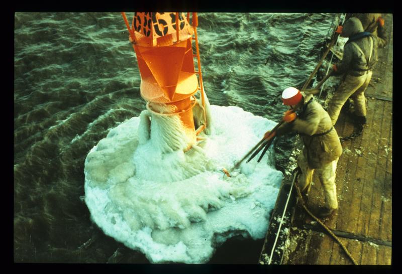 Eine völlig vereiste Tonne im freien Wasser der Ostsee schwimmend, wird vom Tonnenlegerdeck aus vom Eis befreit (1996)