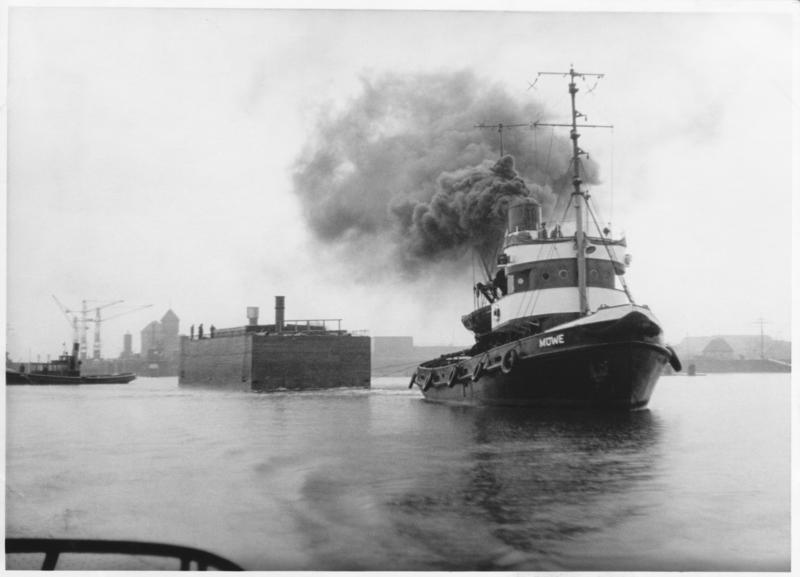 Schwimmkasten wird transportiert vom dampfgetriebenen Schlepper Möwe, im Hintergrund Kiel (1950)