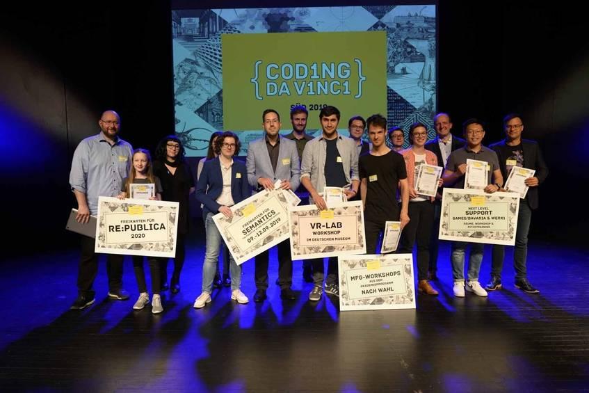 Gewinner und Jury fröhlich vereint auf der Bühne des KunstKulturQuartiers bei der Preisverleihung von Coding da Vinci Süd, Fotografin: Diane von Schoen (CC BY 4.0 International)