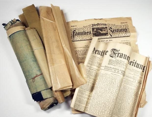 Konvolut mehrerer alter Zeitungsausgaben und Dokumente, zum Teil vergilbt und zerknittert. Bild: Staatliche Museen zu Berlin, Museum Europäischer Kulturen / Michael Mohr