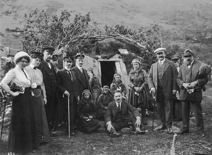 """""""Norwegen. Samenfamilie mit Touristen der Hapag vor ihrer Erdhütte bei Tromsø"""" (1912), Fotograf: Oswald Lübeck, SLUB / Deutsche Fotothek (Public Domain)"""