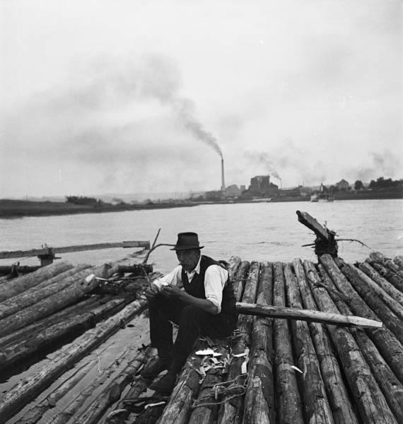 """""""Heidenau. Floß mit sitzendem Flößer auf der Elbe gegen Industriegebiet"""" (1910), Bild: Zöllner, Emil (Fotograf), SLUB/Deutsche Fotothek (Freier Zugang - Rechte vorbehalten)"""
