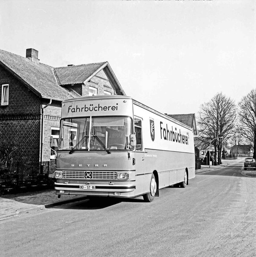 """""""Bücherbus am Straßenrand vor Wohnhaus: im Hintergrund Straßenbäume, parkender Pkw"""" (ca. 1979), Kreisarchiv Stormarn"""